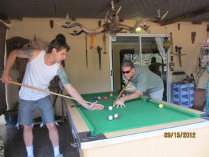 John and Nate playing pool (John's stick is a broom handle)